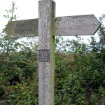A decoratively-illustrated finger post shows the Pirton/Hitchin route